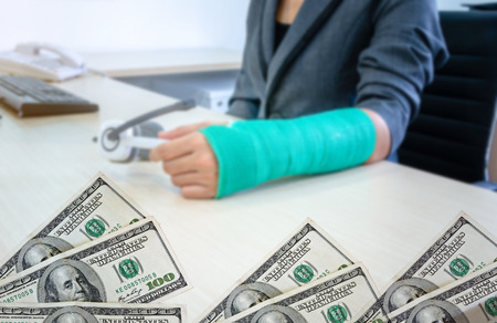 American hundred dollar bills isolated on blurred background woman with broken hand and green cast  holding headphone on desk. Standard-Bild - 112670102