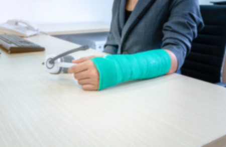 blurred woman with broken hand and green cast  holding headphone on desk. Standard-Bild - 112670105