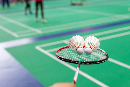 hand holding badminton shuttlecock with racket on court. Standard-Bild - 112670108
