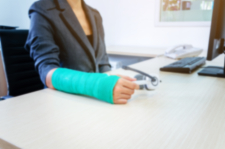 blurred woman with broken hand and green cast  working on computer in office. Standard-Bild - 112670113