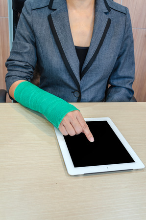 Woman With Broken Hand And Green Cast Working On Tablet Computer