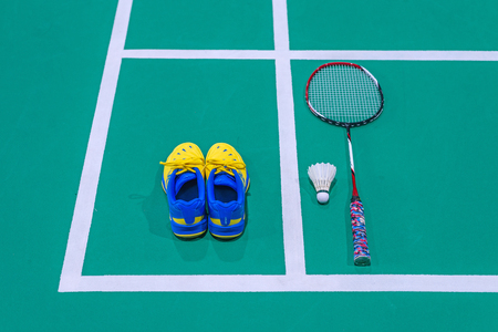 badminton shoes with shuttlecock and racket on court. Stock Photo