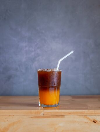Ice coffee, americano coffee with orange in cafe.
