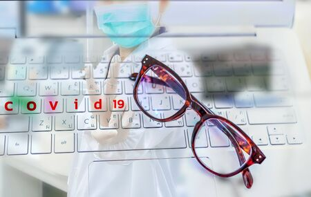 Covid - 19 words and eyeglasses on keyboard computer on laptop with blurred background doctor hands showing victory sign gesture and fight Covid-19 virus Standard-Bild