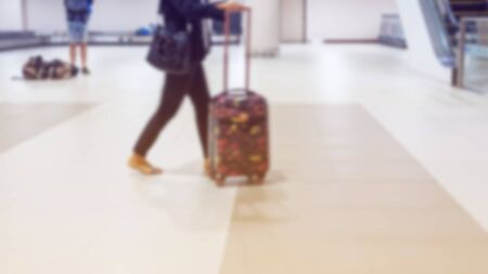 blurred background group of traveler carries luggage at the airport terminal