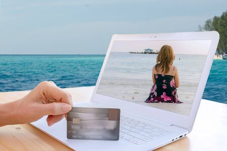Hands holding plastic credit card with modern white laptop and woman on the beach and sitting near the sea.  Online shopping concept. Standard-Bild