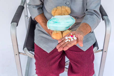 The elderly Asian people with wrinkled and freckled hands holding small teddy bear with face mask and pill on hand. Standard-Bild