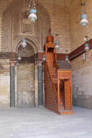 Traditional wooden minbar inside old mosque interior