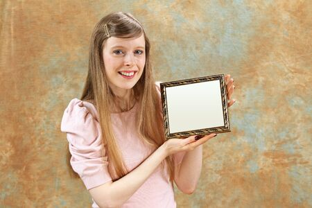Young blonde girl holding empty vintage frame Stock Photo - 11966667