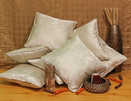 Pile of silk beige pillows on brown background Stock Photo