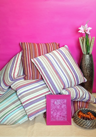 Large pile of stripe pattern pillows against pink wall Stock Photo - 12120332