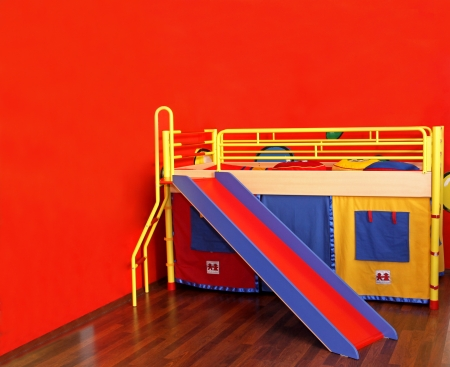 Colorful bed in childs room with red wall