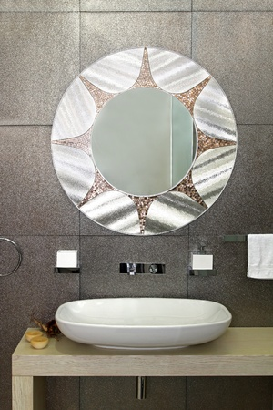 Modern bathroom with sparkling tiles and oval mirror Stok Fotoğraf