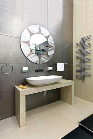 Modern bathroom with sparkling tiles and oval mirror Stock Photo