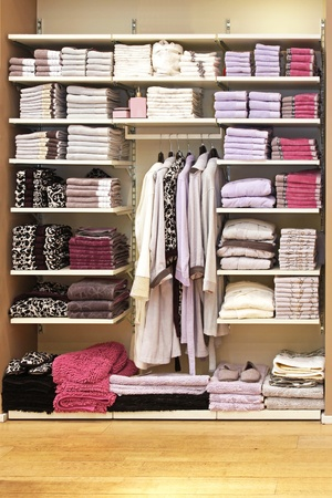 Big storage space with towels on shelf and bathrobes on hangers photo