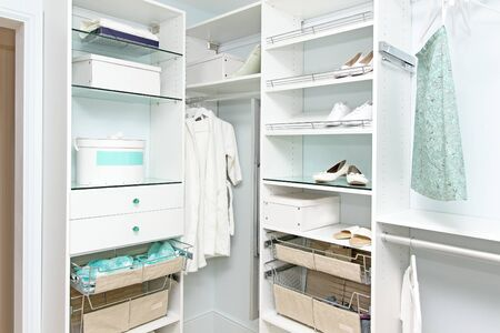 Detail of large walk in closet with modern wardrobe on hangers photo