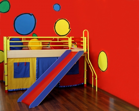 Colorful bed in childs room with red wall and sledge