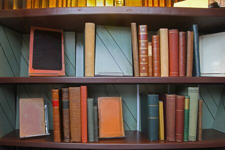 Old grunge books in leather binding on library shelf photo