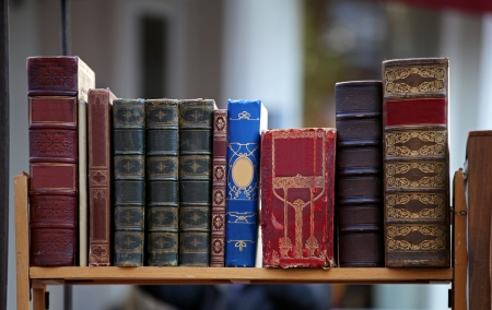 Old grunge books with leather binding on wooden shelf Stock Photo