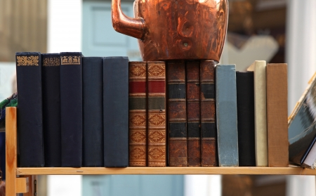 Old grunge books in leather binding on wooden shelf photo