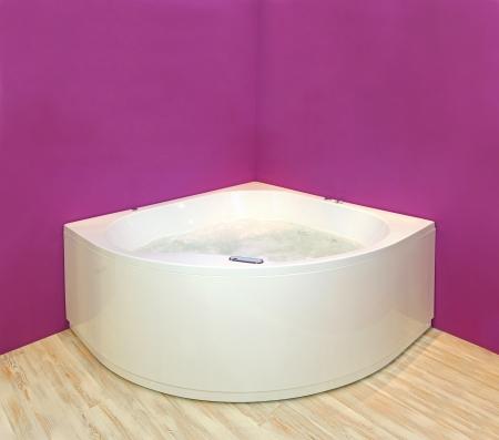 hydromassage: Modern corner hydromassage bathtub with pink wall interior Stock Photo