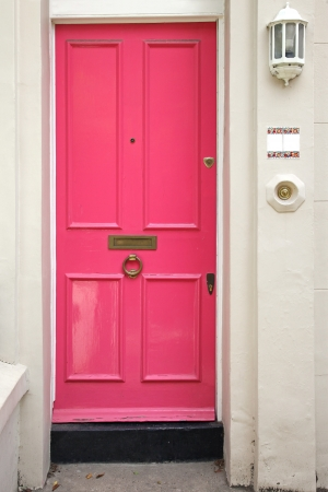 Pink entrance door in front of residential house