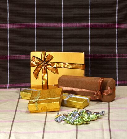 Present and chocolate boxes with gold ribbon photo