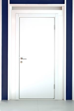 Modern white entrance door with silver knob photo