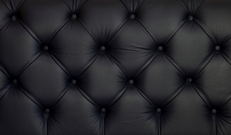 padding: Detailed texture of creased black leather upholstery