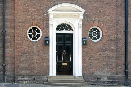 Old brick wall house with black entrance door