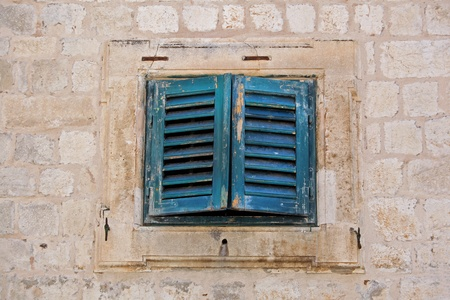 Grunge old window with closed wooden blinds and stone facade photo