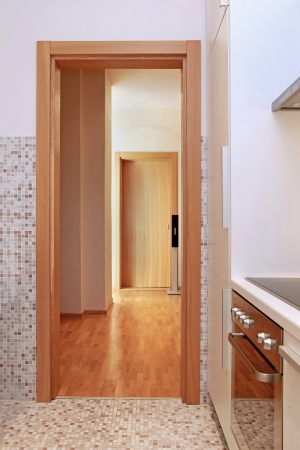 Wooden entrance frame to contemporary kitchen interior photo