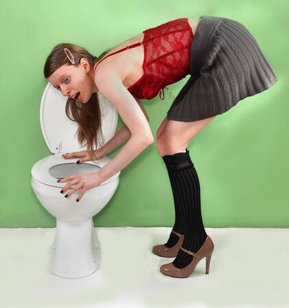 vomit: Young woman leaning to vomit over toilet after drunken night out