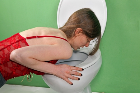Young skinny girl suffering from bulimia vomiting in the bathroom