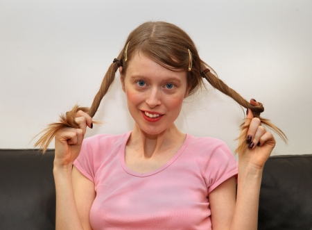 Blonde teenage girl smiling and rolling her pigtails photo