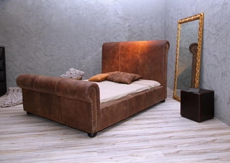 Vintage bedroom interior with leather bed and mirror