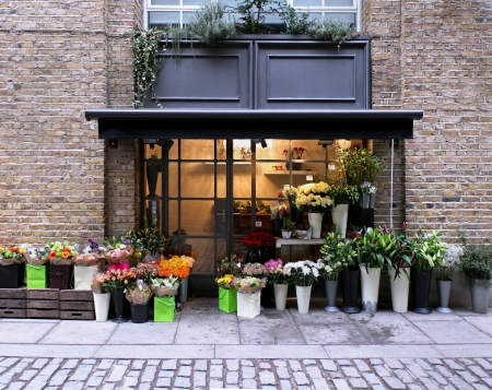 Flower shop exterior in street with brickwall facade Editorial