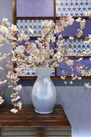 Decorative vase with white flowers on wooden shelf Stock Photo - 19443279