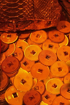 coins pile: Ancient golden Chinese coins pile near gold case
