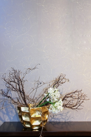 Gold decorative vase with dry flowers on wooden shelf Stock Photo - 21512646