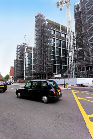 London, United Kingdom - May 27, 2009; Famous black cab on London street with Hyde Park One complex under construction in background