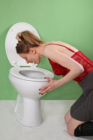 Young bulimic skinny girl vomiting over toilet Stock Photo - 24144913