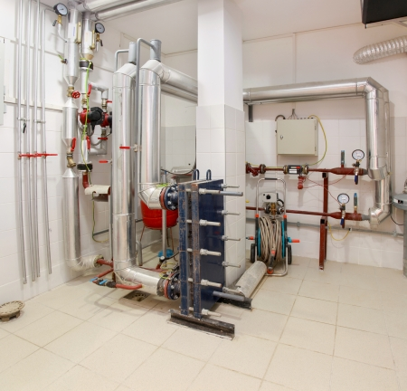 Utility room in house basement withboilers and pipes Imagens