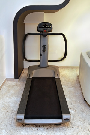 Modern treadmill machine inside home gym interior photo