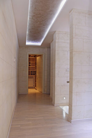 walk in closet: Long corridor in luxury house interior leading towards walk in closet