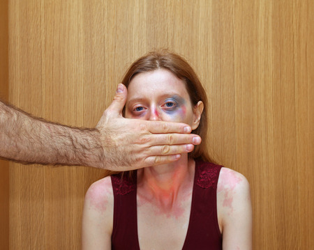 beaten woman: Abused beaten woman keeping silent by man holding hand over her mouth Stock Photo
