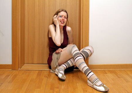 beaten woman: Terrified young woman sitting on the appartment floor after beaten up Stock Photo