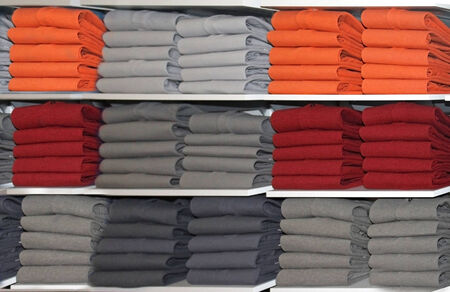 neatly: Colorful neatly folded t-shirts on shelf in retail store