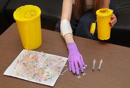 Trabajador Medicina eliminación de desechos médicos en contenedores de plástico con guante de protección Foto de archivo