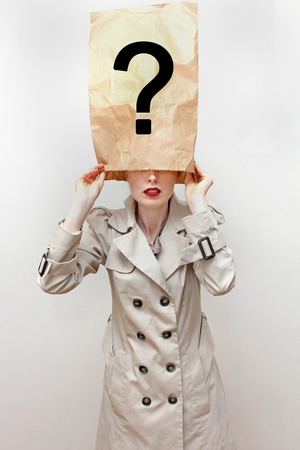 hides: Young woman in trench coat hides her identity with face covered under paper bag with question mark